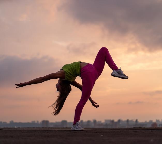 Femme flexible faisant des poses en plein air sur le concept de fond de coucher de soleil dramatique de bonheur et de joie