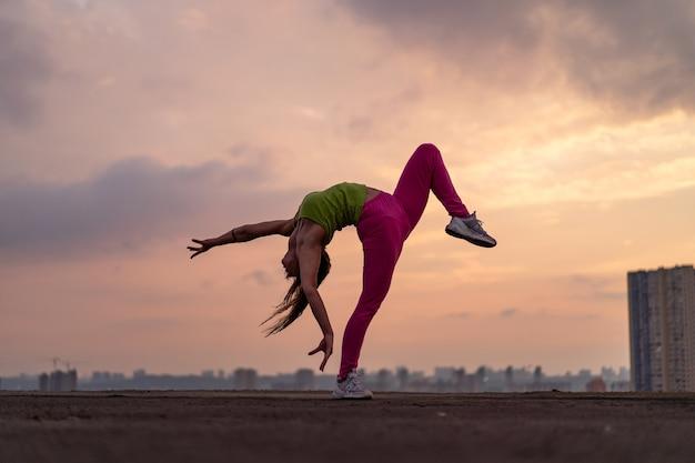 Femme flexible faisant des poses en plein air sur le concept de fond dramatique coucher de soleil d'activité, santé