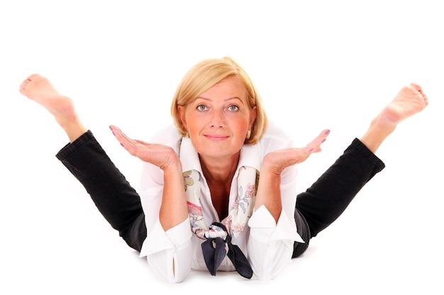 Une femme flexible mature allongée sur fond blanc
