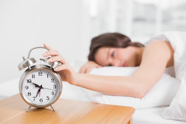 Femme floue dans son lit, étendant la main au réveil