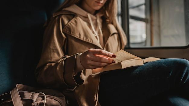Femme floue lisant un livre à l'intérieur d'un train