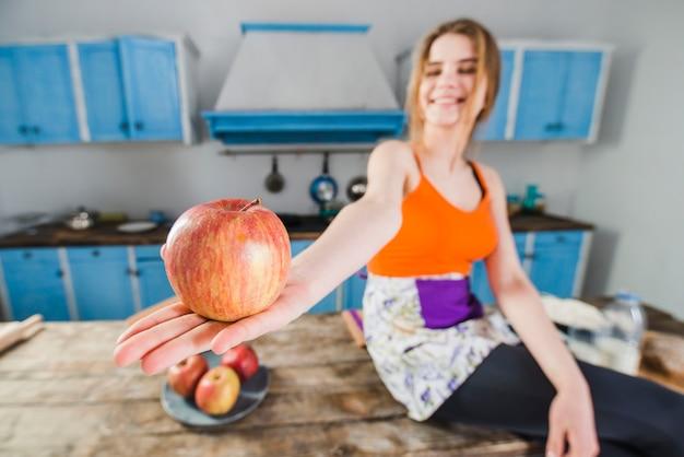 Femme floue montrant la pomme
