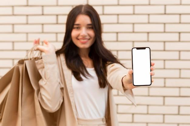 Femme floue montrant téléphone mobile espace copie