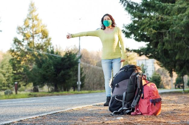 Femme floue portant un masque protecteur en auto-stop sur une route rurale.