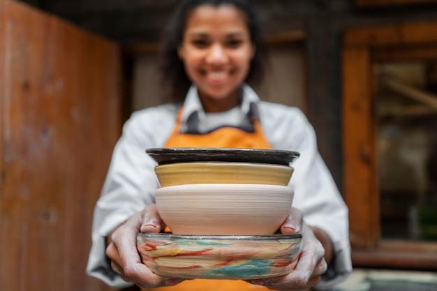 Femme floue tenant des pots en argile