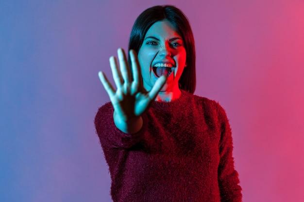 Femme folle effrayée debout avec la main tendue, montrant un geste d'arrêt et criant