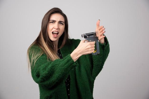 Femme folle tenant un outil de travail sur fond gris.