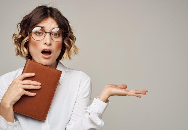 Femme sur fond gris avec un livre dans ses mains et portant des lunettes copy space