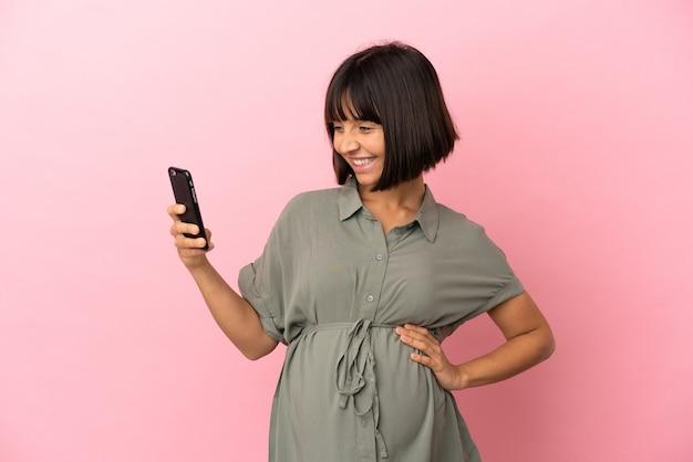 Femme sur fond isolé enceinte et à l'aide de téléphone mobile