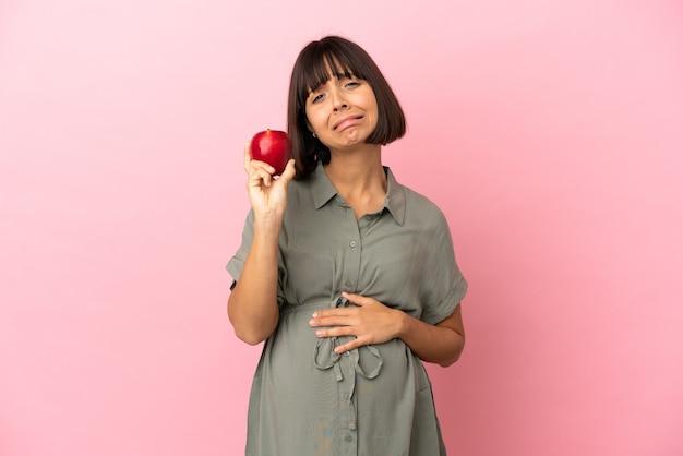 Femme sur fond isolé enceinte et frustrée en tenant une pomme