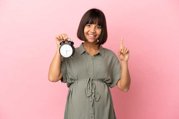 Femme sur fond isolé enceinte et tenant l'horloge tout en comptant un