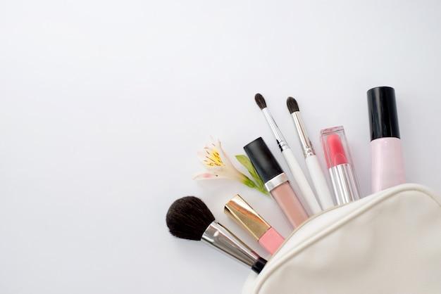 Femme fond plat maquillage avec cosmétiques, espace copie.
