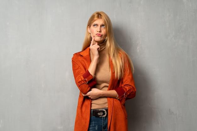 Femme sur fond texturé souriant et regardant vers l'avant avec un visage confiant