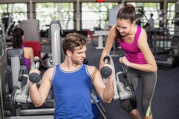 Femme de formateur aidant un homme sportif dans une salle de sport