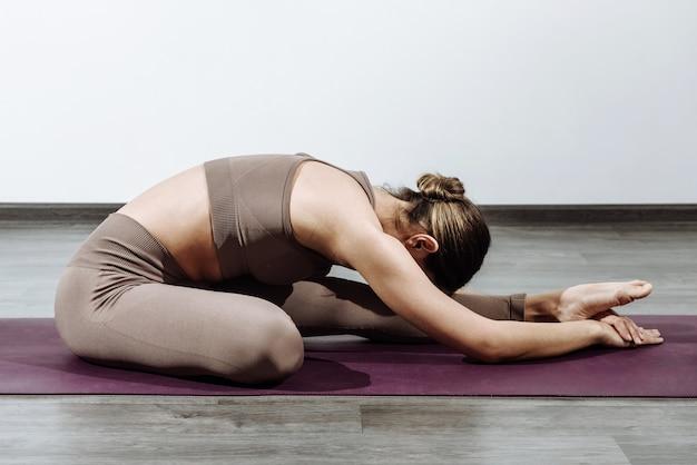 Femme formateur faisant du yoga sur le tapis appuyé sur une jambe droite