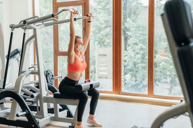 Femme à la formation de gym avec masque facial