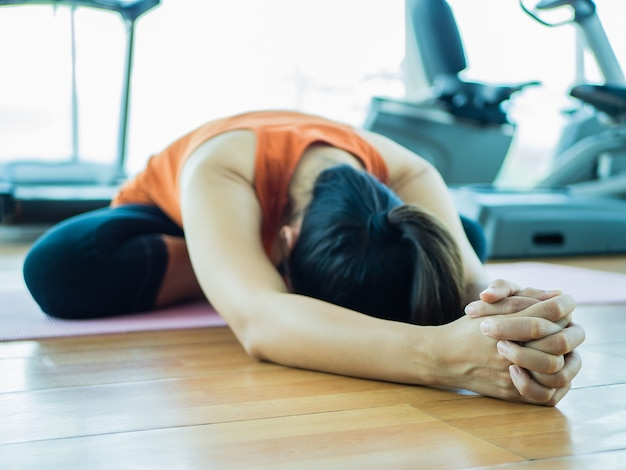 Femme formation yoga avec fond d'équipement de fitness