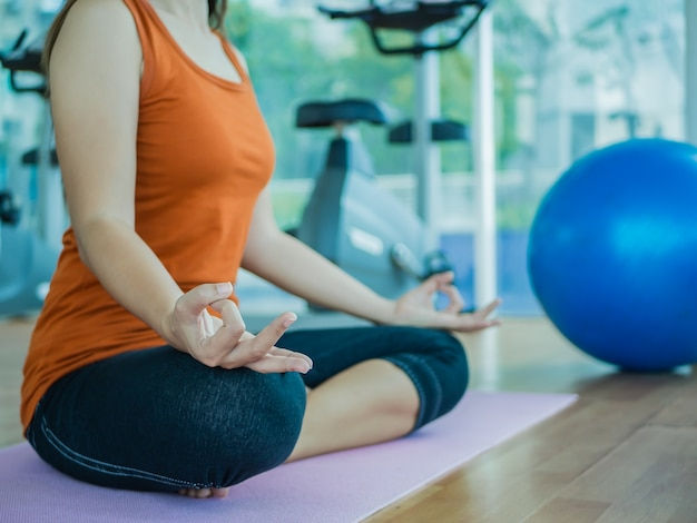 Femme formation yoga et méditation avec fond d'équipement de fitness