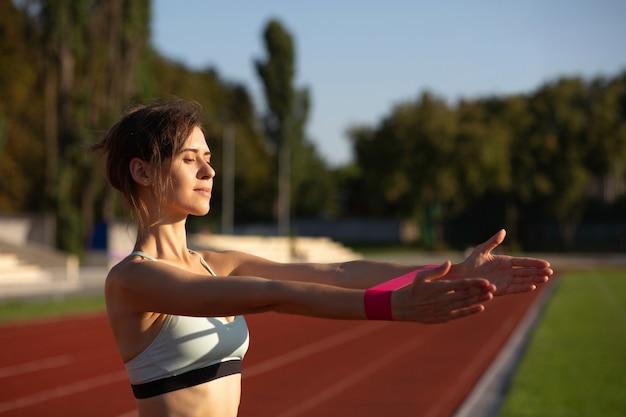 Femme en forme adulte faisant de l'exercice avec les mains avec une bande de résistance