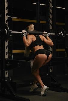 Une femme en forme aux cheveux blonds abaisse la barre après s'être accroupie dans le squat rack d'une salle de sport. une fille fait une séance d'entraînement des jambes.