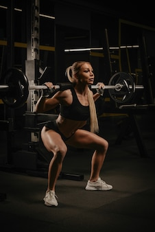 Une femme en forme aux cheveux blonds s'accroupit avec une barre près du support de squat dans une salle de sport. une fille fait une séance d'entraînement des jambes.