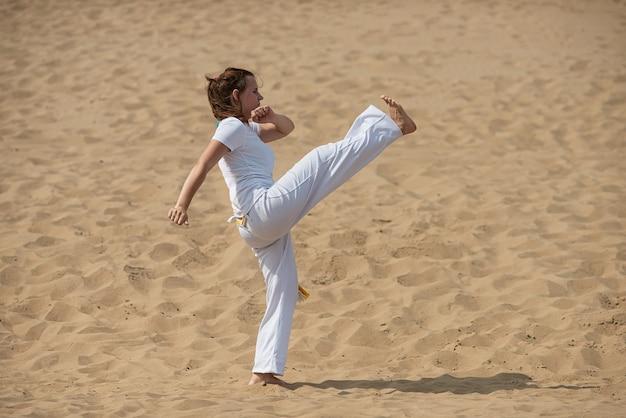 Femme forme la capoeira en plein air. fille effectue un coup de pied