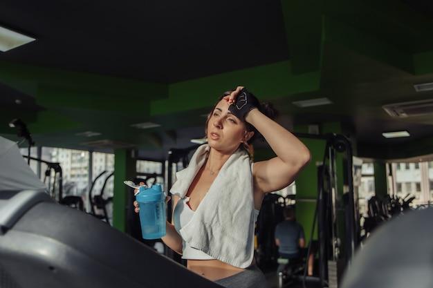 Femme en forme fatiguée avec une serviette sur ses épaules tenant une bouteille d'eau sur un tapis roulant. concept de perte de poids, entraînement aérobie