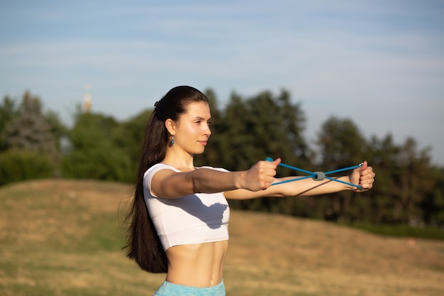Femme en forme glorieuse faisant des exercices d'étirement avec une bande de résistance