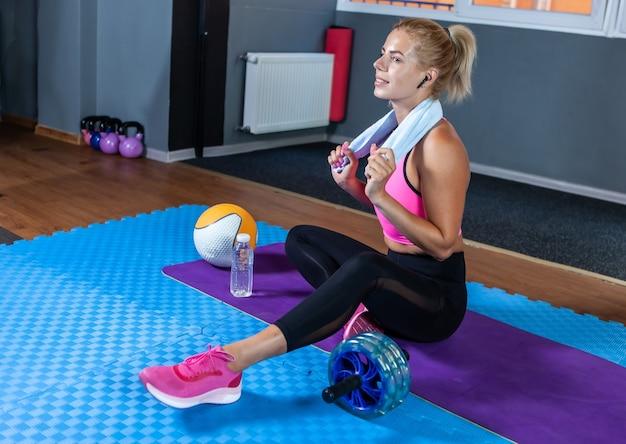 Femme en forme joyeuse assise sur un tapis se reposant après l'entraînement avec une serviette autour du cou