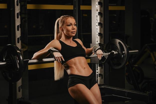 Une femme en forme avec de longs cheveux blonds est posée sur une barre au squat rack dans une salle de sport