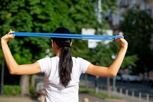 Femme en forme merveilleuse faisant de l'exercice avec les mains avec une bande de résistance élastique dans le parc