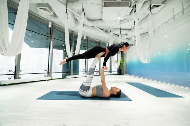 Femme forte. deux femmes fortes et en forme portant des leggings pratiquant le yoga fitness ensemble