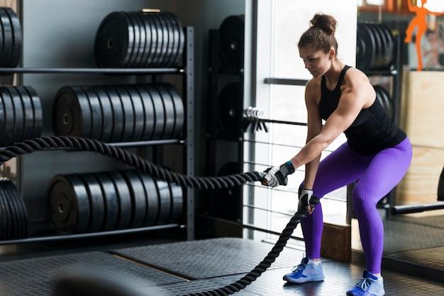 Femme forte exerçant avec des cordes