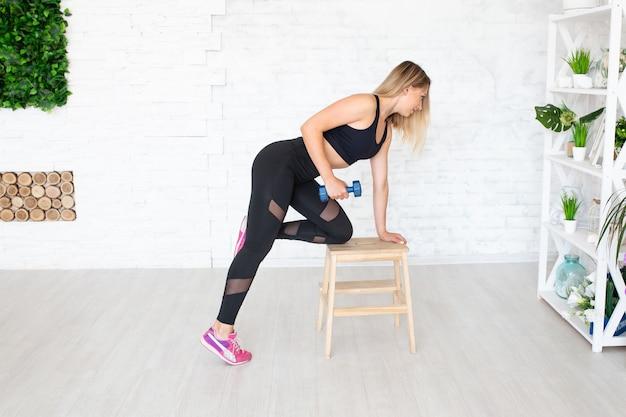 Femme forte faisant de l'exercice avec des haltères. beau jeune modèle de fitness musculaire sportif