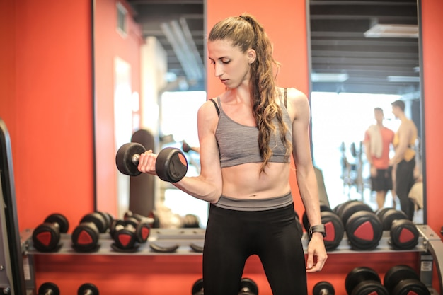 Femme forte, soulever des poids dans la salle de sport