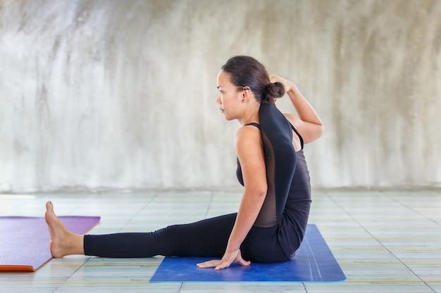 Femme forte stagiaire asiatique pratiquant une pose difficile de yoga dans un fond concret