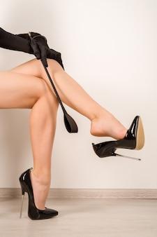 Femme avec fouet en talons aiguilles noirs