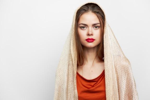 Femme avec un foulard glamour lèvres rouges regarder vers l'avant modèle avec des cosmétiques sur le visage vue de face
