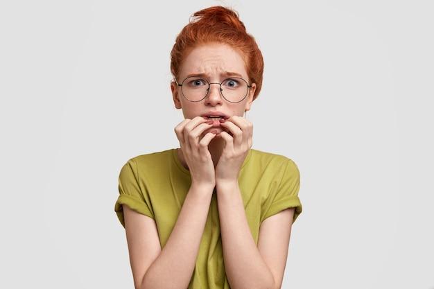 Une femme foxy inquiète regarde nerveusement la caméra, garde les mains près de la bouche, étant intriguée par quelque chose, habillée en tenue décontractée