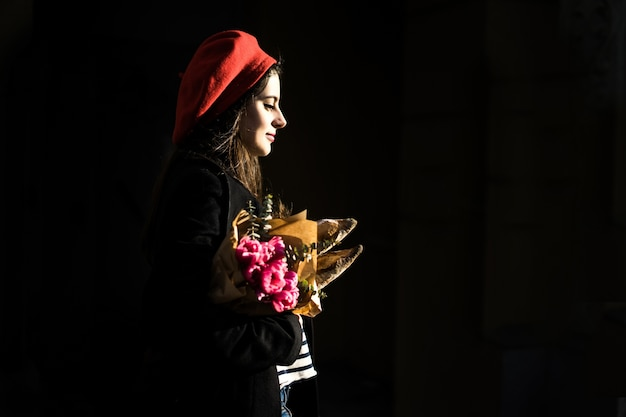 Femme française avec des baguettes dans la rue en béret