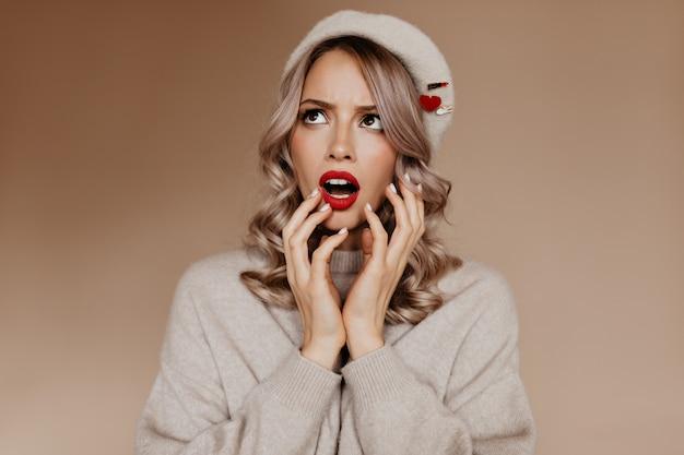 Femme française avec des boucles parfaites exprimant l'étonnement