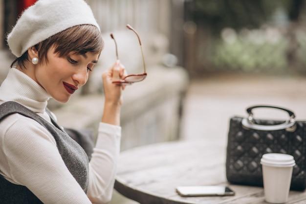 Femme française buvant du café au café sur la terrasse