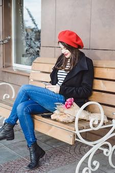 Femme française dans un béret rouge sur un banc de rue