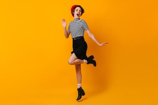 Femme française insouciante en jupe danse sur mur jaune