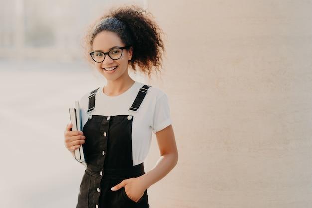 Femme frisée aux cheveux peignés, vêtue d'un t-shirt blanc, sarafan, garde la main dans la poche, livre et manuel