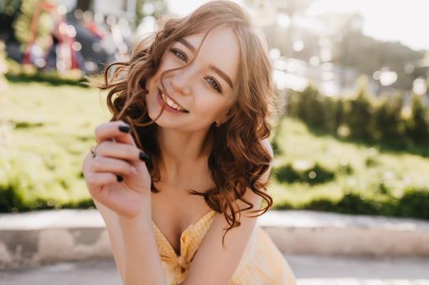 Femme frisée aux cheveux roux intéressé souriant en matinée ensoleillée. adorable modèle féminin de gingembre passant la journée d'été dans le parc.