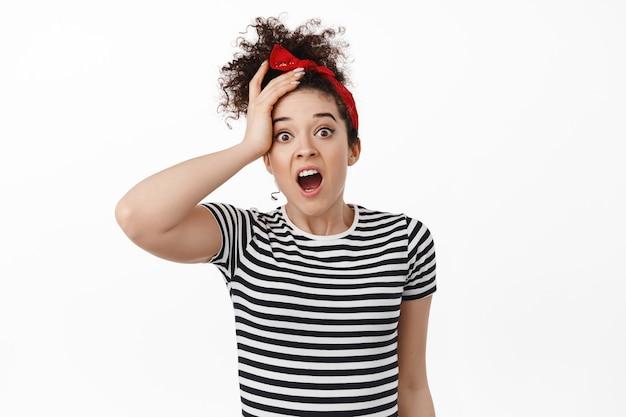 Femme frisée brune choquée avec la main touchant sa tête