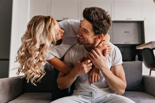 Femme frisée jocund embrassant son mari avec amour. homme brune regardant petite amie avec le sourire.