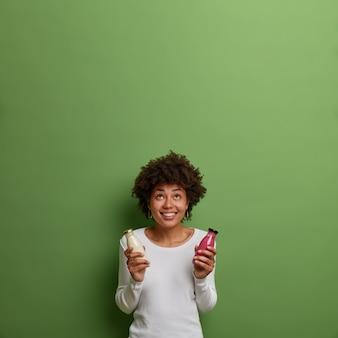 Une femme frisée positive tient un smoothie et du lait végétalien, boit une boisson de désintoxication, a une alimentation équilibrée, concentrée au-dessus avec un large sourire, voit quelque chose d'agréable, isolé sur un mur vert