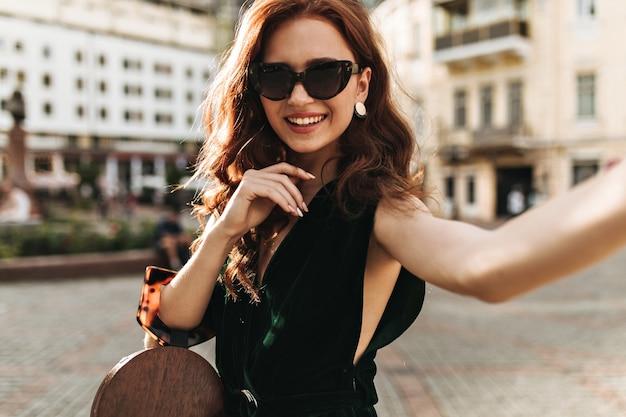 Femme frisée en robe de velours tient le sac à main et prend selfie à l'extérieur